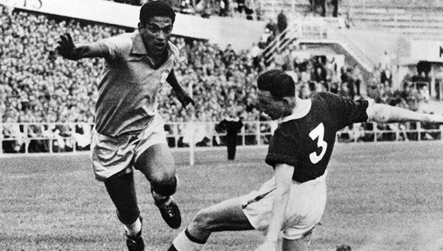 Brazilian forward Garrincha (L) dribbles