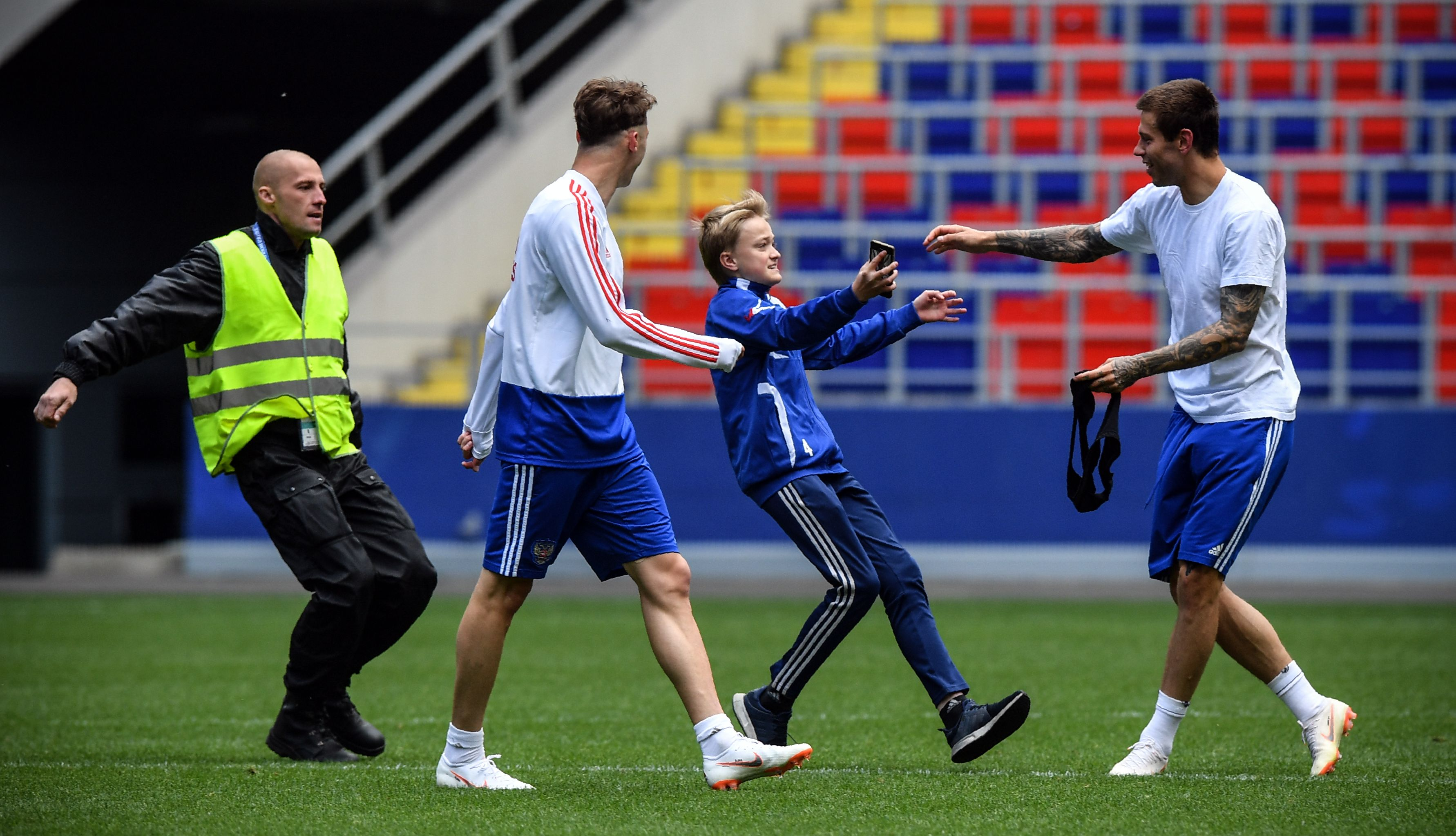 Russia's forward Fyodor Smolov (R) protects a boy as security personnel try to detain him at the pitch during a training session of the Russian national football team at Moscow's VEB Arena stadium on June 9, 2018, ahead of the Russia 2018 World Cup. / AFP PHOTO / Alexander NEMENOV