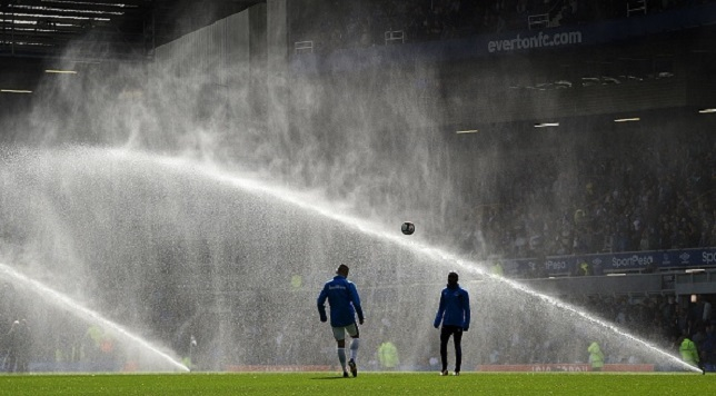 Everton players warm up on the pitch as jets spray water at half-time during the English Premier League football match between Everton and Stoke City at Goodison Park in Liverpool, north west England on August 12, 2017. / AFP PHOTO / Oli SCARFF / RESTRICTED TO EDITORIAL USE. No use with unauthorized audio, video, data, fixture lists, club/league logos or 'live' services. Online in-match use limited to 75 images, no video emulation. No use in betting, games or single club/league/player publications. / (Photo credit should read OLI SCARFF/AFP/Getty Images)