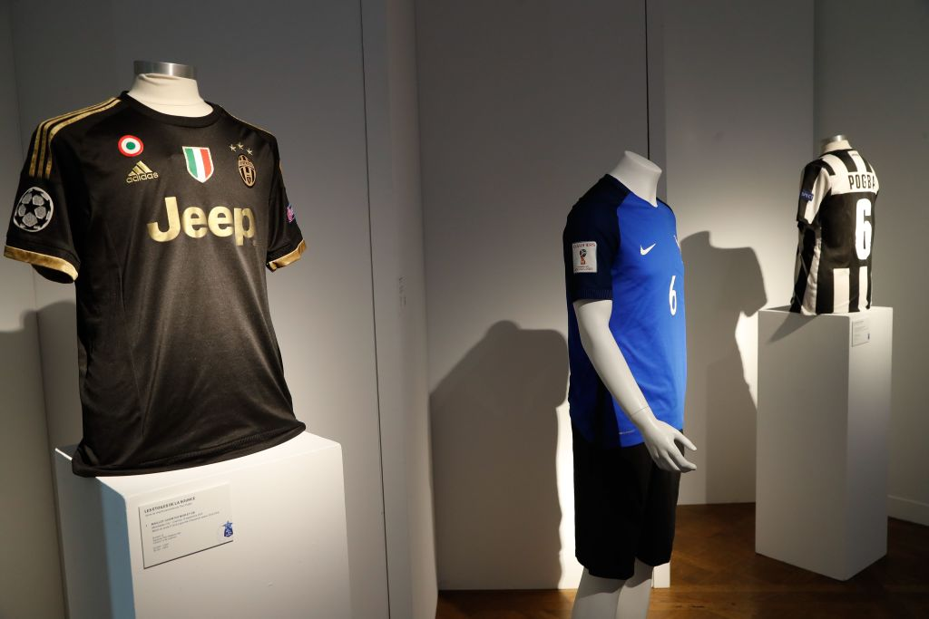 """A French national football team (C) and Juventus jerseys worn by French midfielder Paul Pogba are displayed at Christies auction house on April 26, 2019 in Paris, three days before being auctioned to benefit """"Les étoiles de la Source"""", a charitable organisation working towards better integration for underprivileged children and young people in France through its cultural and sports programmes. - Displayed from left: Juventus shirt worn on September 15, 2015 against Manchester City during a Champions League group D match, shirt of France football team worn on August 31, 2017 against the Netherlands during the 2018 World Cup qualification group A match 7, and a Juventus shirt worn on April 10, 2013 against Bayern Munich during a Champions League quarter final match. (Photo by FRANCOIS GUILLOT / AFP)        (Photo credit should read FRANCOIS GUILLOT/AFP/Getty Images)"""