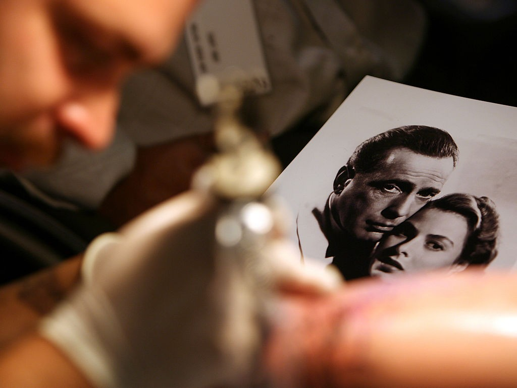 A tattoo artist works on a client from a