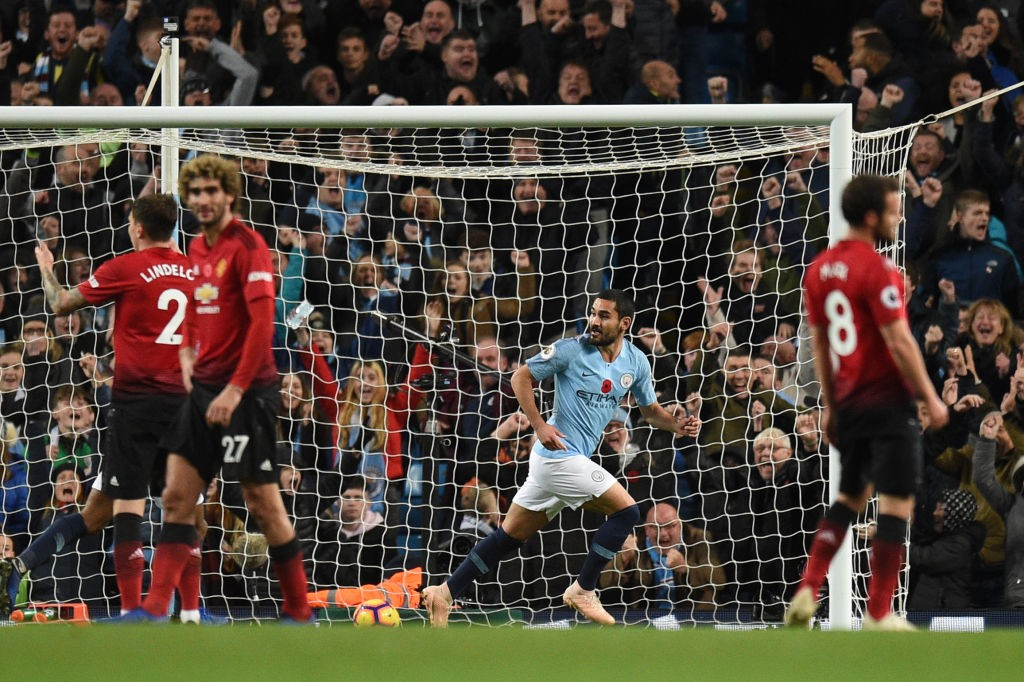 Manchester City's German midfielder Ilkay Gundogan (C) celebrates after scoring their third goal during the English Premier League football match between Manchester City and Manchester United at the Etihad Stadium in Manchester, north west England, on November 11, 2018. (Photo by Oli SCARFF / AFP) / RESTRICTED TO EDITORIAL USE. No use with unauthorized audio, video, data, fixture lists, club/league logos or 'live' services. Online in-match use limited to 120 images. An additional 40 images may be used in extra time. No video emulation. Social media in-match use limited to 120 images. An additional 40 images may be used in extra time. No use in betting publications, games or single club/league/player publications. /         (Photo credit should read OLI SCARFF/AFP via Getty Images)